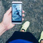Auf dem Bild ist ein Jogger zu sehen, der auf eine Fitness-App schaut.