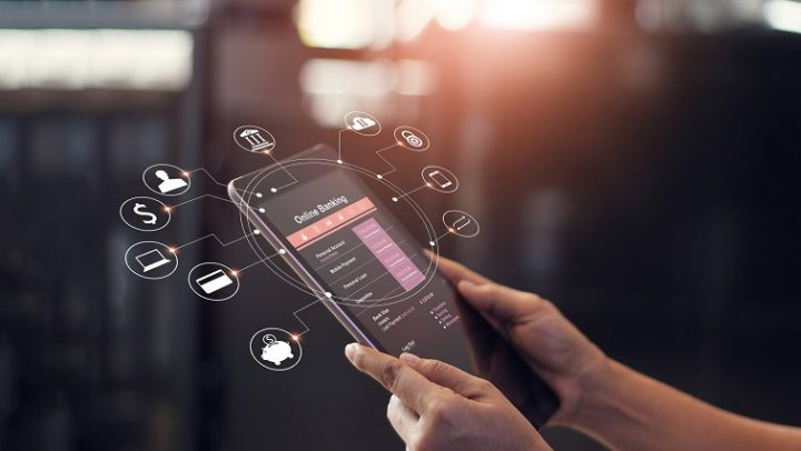 Zwei Hände halten ein Tablet auf dem Online Banking aufgerufen ist.