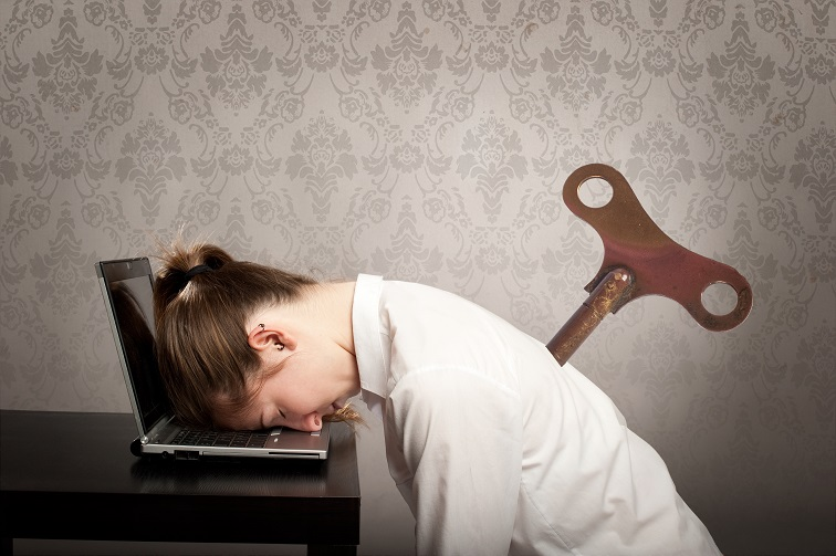 Geschäftsfrau mit dem Kopf auf dem Laptop und einem Schlüssel im Rücken